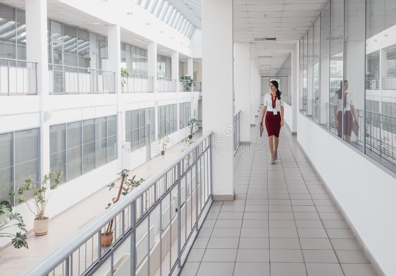 Affärskvinna som promenerar kontorskorridoren Le bakgrund för affärskvinnaGoes Against White kontor En ung nätt flicka royaltyfria foton