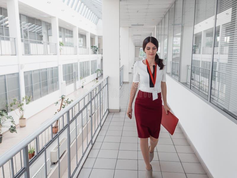 Affärskvinna som promenerar kontorskorridoren Le bakgrund för affärskvinnaGoes Against White kontor En ung nätt flicka royaltyfri foto