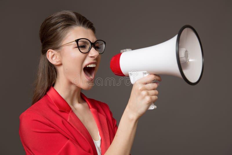Affärskvinna som ropar på en megafon Ung nätt flicka i exponeringsglas och ett rött omslag royaltyfri foto