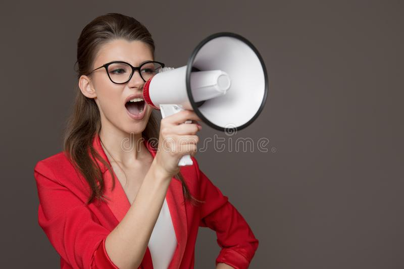 Affärskvinna som ropar på en megafon Ung nätt flicka i exponeringsglas och ett rött omslag arkivfoton