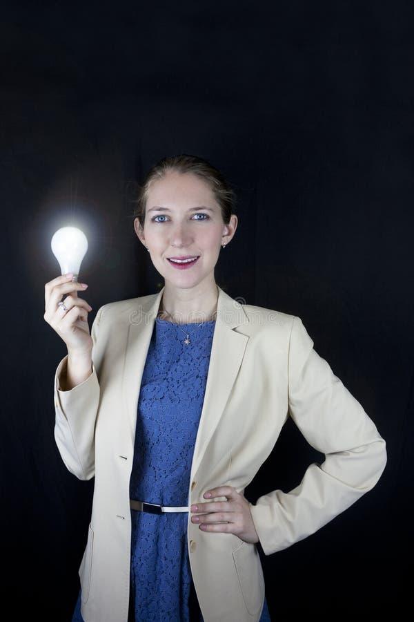Affärskvinna som rymmer den ljusa kulan arkivbild