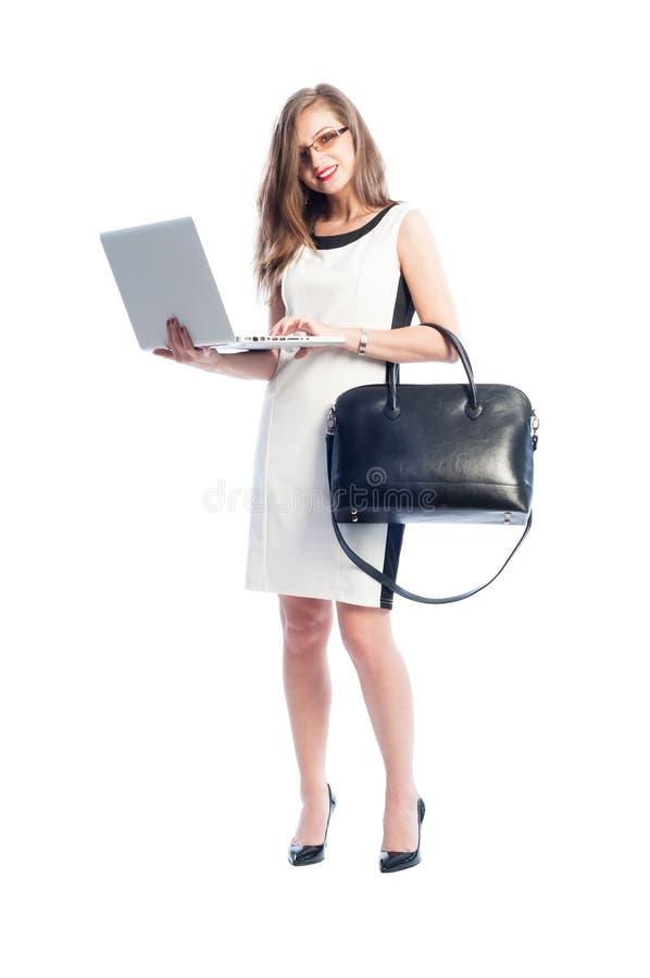 Affärskvinna som rymmer en öppen bärbar dator, medan stå royaltyfri fotografi