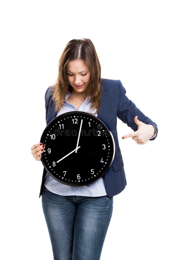 Affärskvinna som rymmer en stor klocka arkivfoto