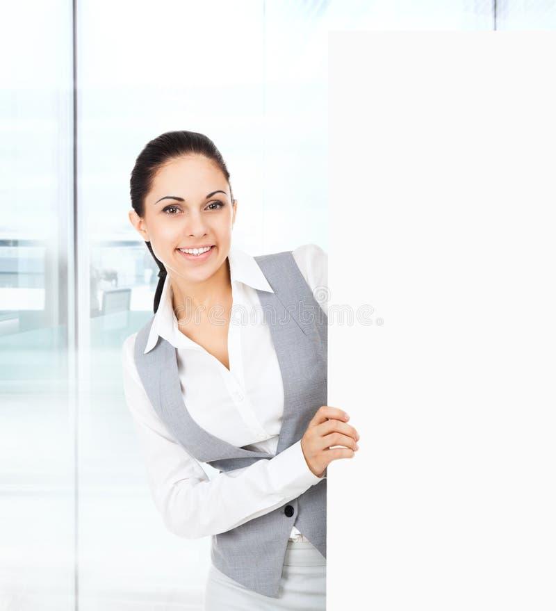 Affärskvinna som rymmer ett tomt vitt kortbräde royaltyfri foto