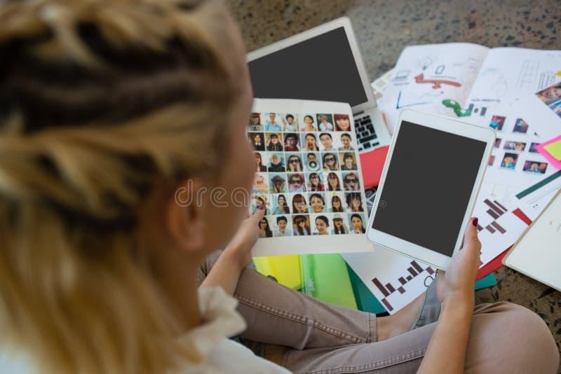 Affärskvinna som rymmer fotografier och den digitala minnestavlan på kontoret fotografering för bildbyråer