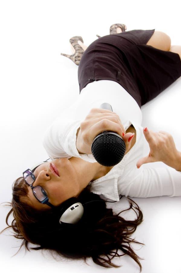 affärskvinna som rymmer ner den liggande mikrofonen royaltyfri fotografi