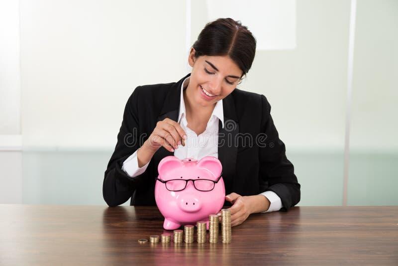 Affärskvinna som sätter in myntet i piggybank royaltyfri fotografi