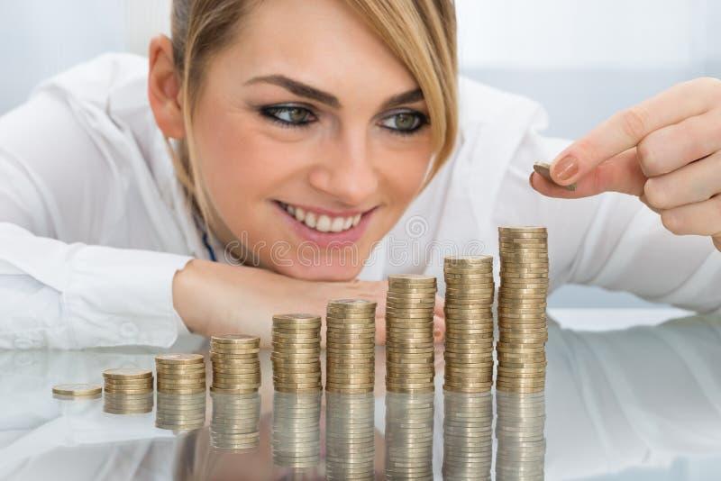 Affärskvinna som sätter myntet på bunt av mynt arkivbild