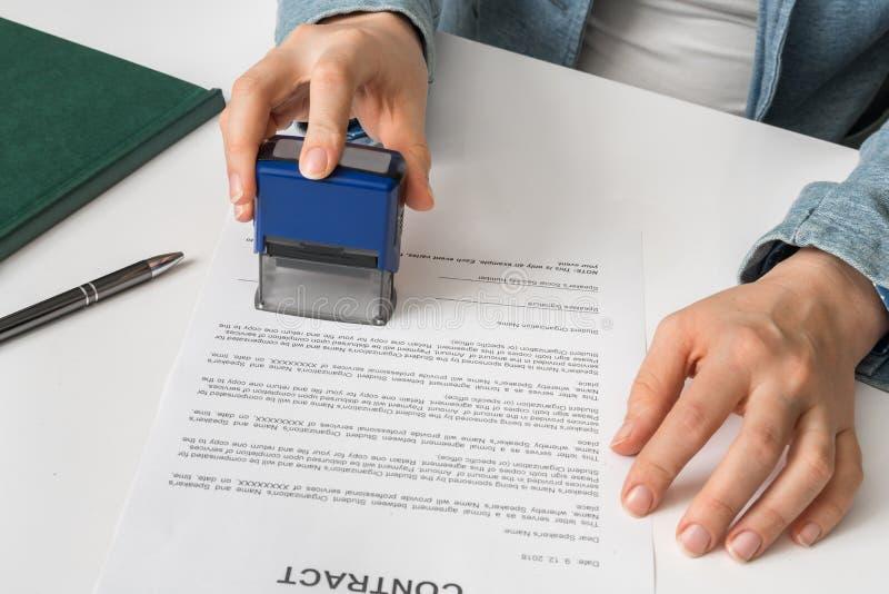 Affärskvinna som sätter stämpeln på dokument i kontoret royaltyfria bilder