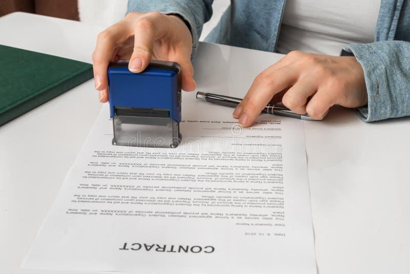 Affärskvinna som sätter stämpeln på dokument i kontoret arkivfoton