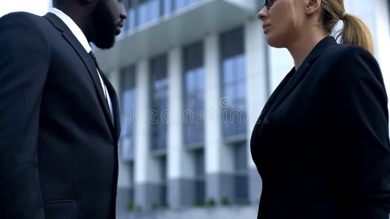 Affärskvinna som ser allvarligt afro--amerikan anställd, problem på arbete royaltyfri fotografi