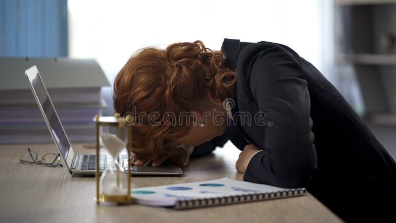 Affärskvinna som ser bärbara datorn som ligger på tabellen, utmattning, stopptidtryck arkivbilder