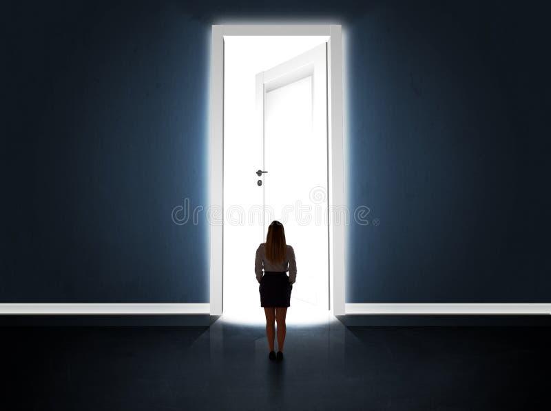 Affärskvinna som ser den stora ljusa öppnade dörren arkivfoto
