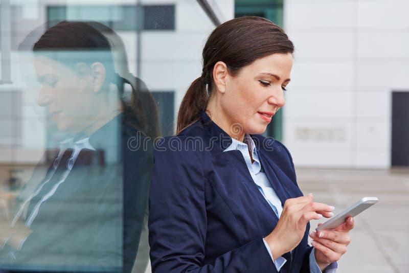 Affärskvinna som ser hennes smartphone royaltyfria foton