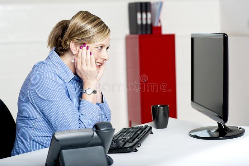 Affärskvinna som ser in i datorskärmen arkivbilder