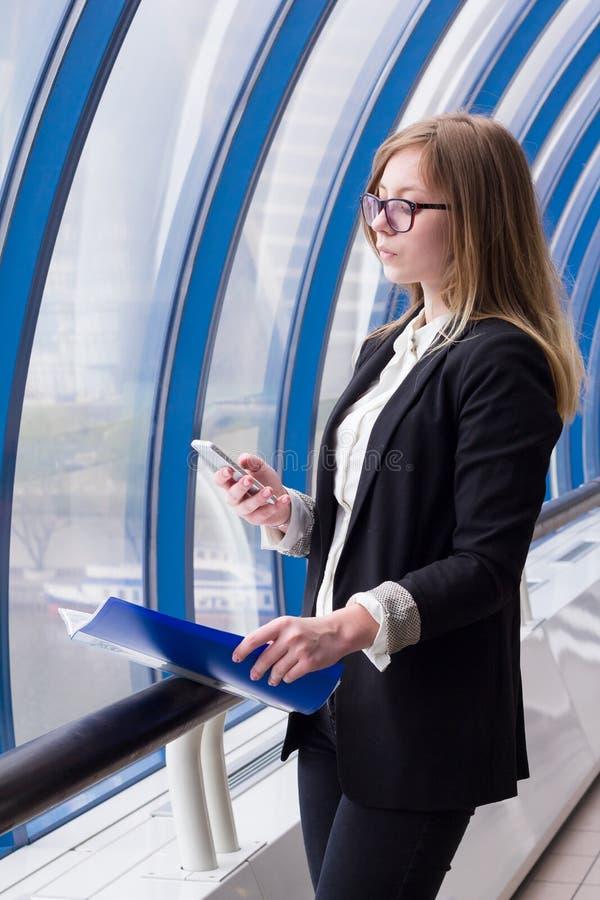 Affärskvinna som ser telefonen med en mapp med dokument i hand arkivbild