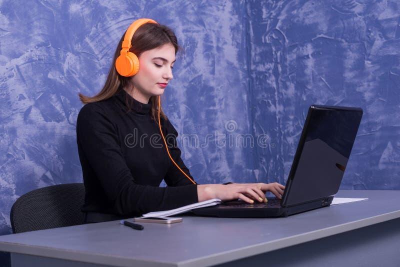 Affärskvinna som sitter i hörlurar och arbetar på en bärbar dator, avlägset arbete royaltyfria bilder