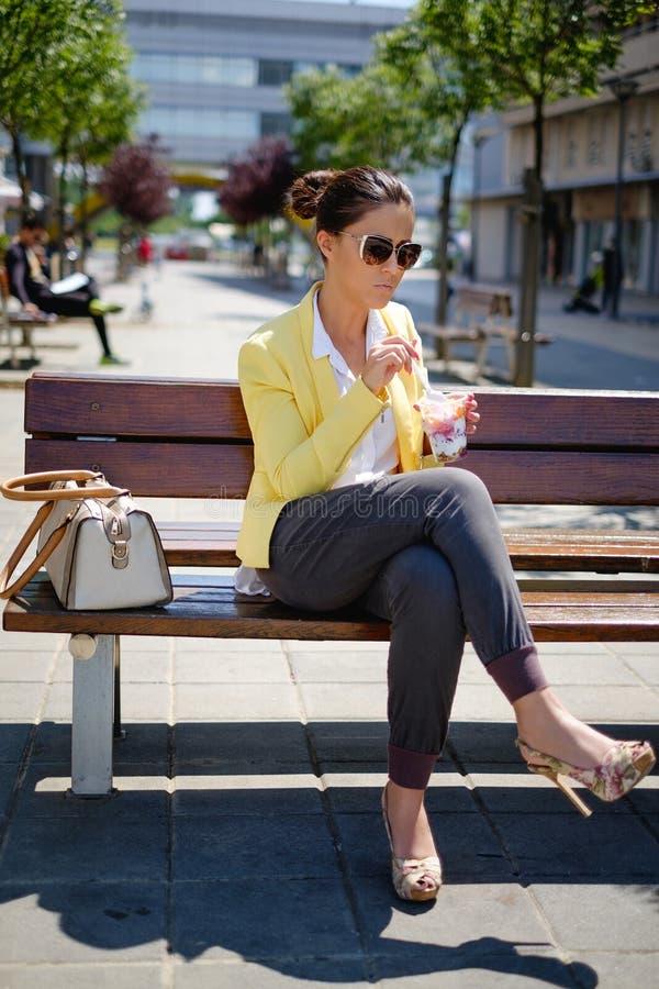 Affärskvinna som sitter och äter sund mat arkivbild