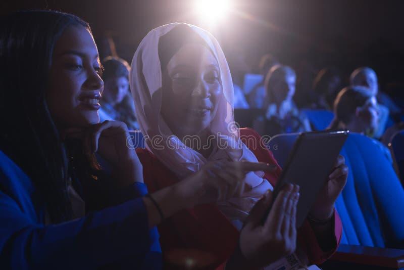 Affärskvinna som sitter och ser den digitala minnestavlan i salongen royaltyfria bilder