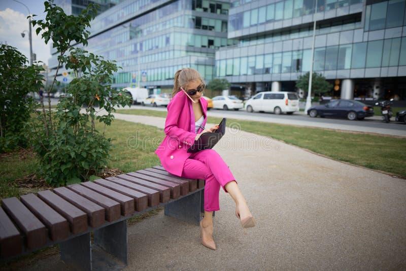 Affärskvinna som sitter på en bänk i gatan arkivbild