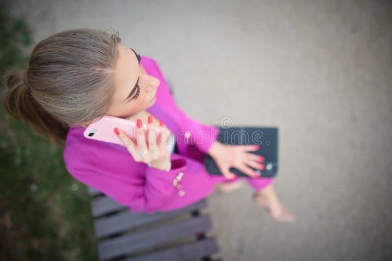 Affärskvinna som sitter på en bänk i gatan arkivfoto
