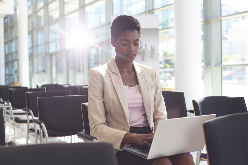 Affärskvinna som sitter på stol och använder bärbara datorn i lobby royaltyfri foto