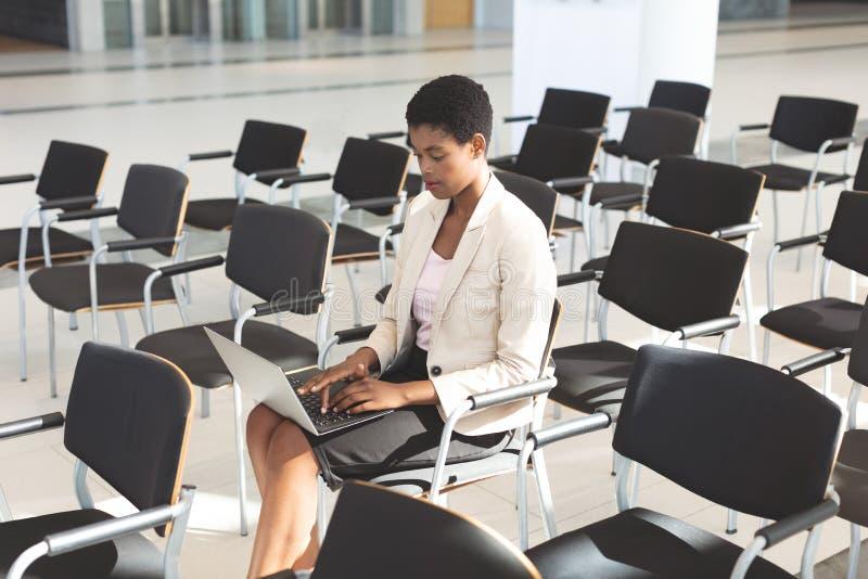 Affärskvinna som sitter på stol och använder bärbara datorn i lobby arkivbild
