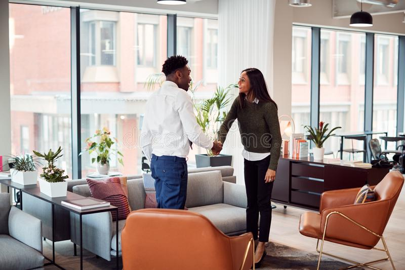 Affärskvinna som skakar hand med manlig intervju som kandiderar till sittplatsen i det moderna kontoret royaltyfria bilder