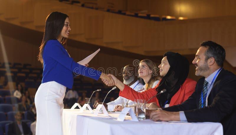 Affärskvinna som skakar handen till affärskollegan i salongen royaltyfri fotografi