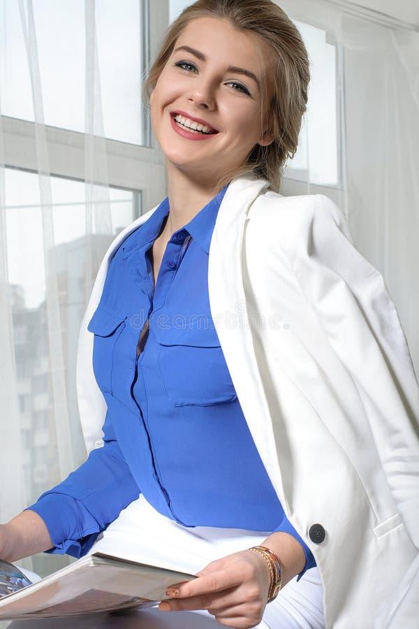 Affärskvinna som skrattar, medan läsa en tidskrift Hon bär arkivbild