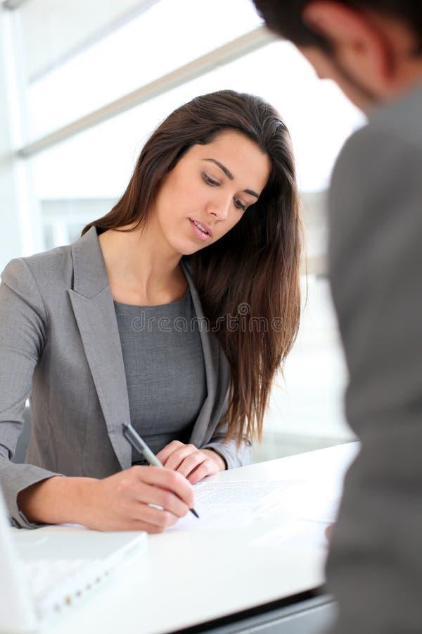 Affärskvinna som skriver ett dokument för partner royaltyfria bilder