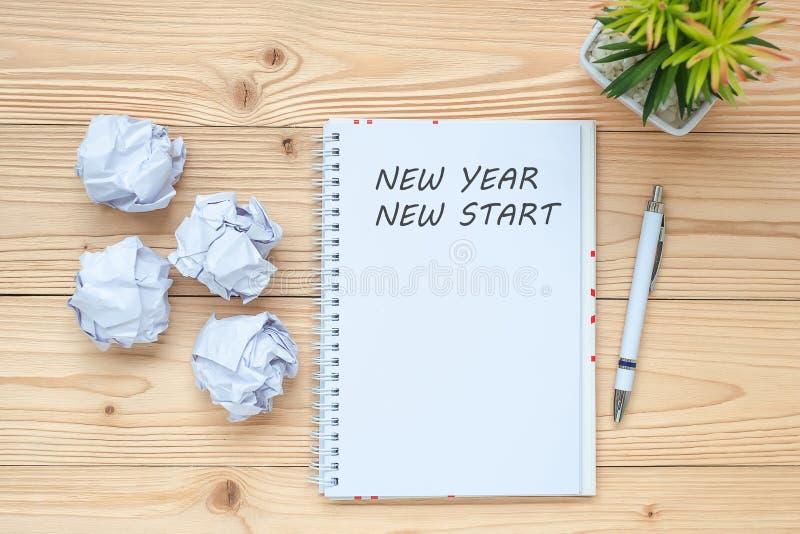 Affärskvinna som skriver ny start för nytt år med anteckningsboken, smulat papper och koppen för svart kaffe på tabellen Idérikt  royaltyfri bild
