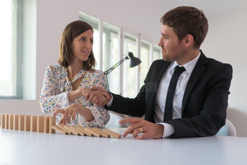 Affärskvinna som stoppar fallande dominobrickor royaltyfria bilder