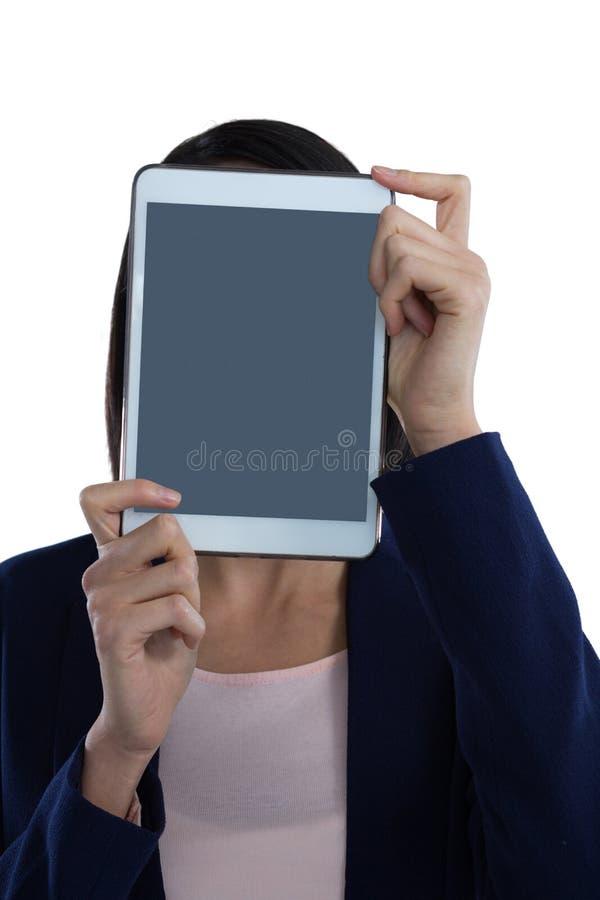 Affärskvinna som täcker hennes framsida med den digitala minnestavlan royaltyfria foton
