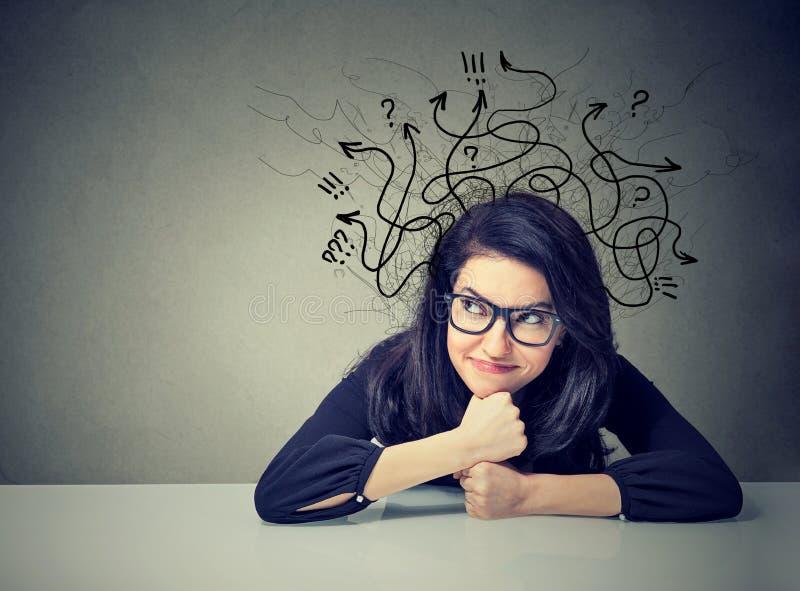 Affärskvinna som tänker beskåda ett lösningssammanträde på tabellen royaltyfria bilder