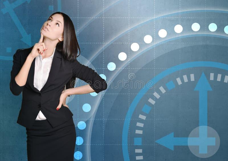 Affärskvinna som tänker på bakgrund av klockan royaltyfria bilder