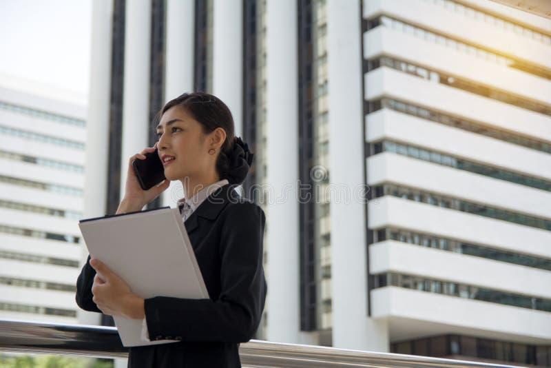 Affärskvinna som talar över den smarta telefonen fotografering för bildbyråer