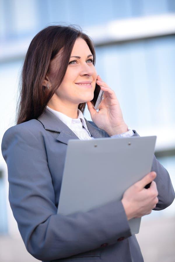 Affärskvinna som talar på den smarta telefonen Arbetare för kontor för affärsfolk som talar på att le för smartphone som är lyckl arkivfoto