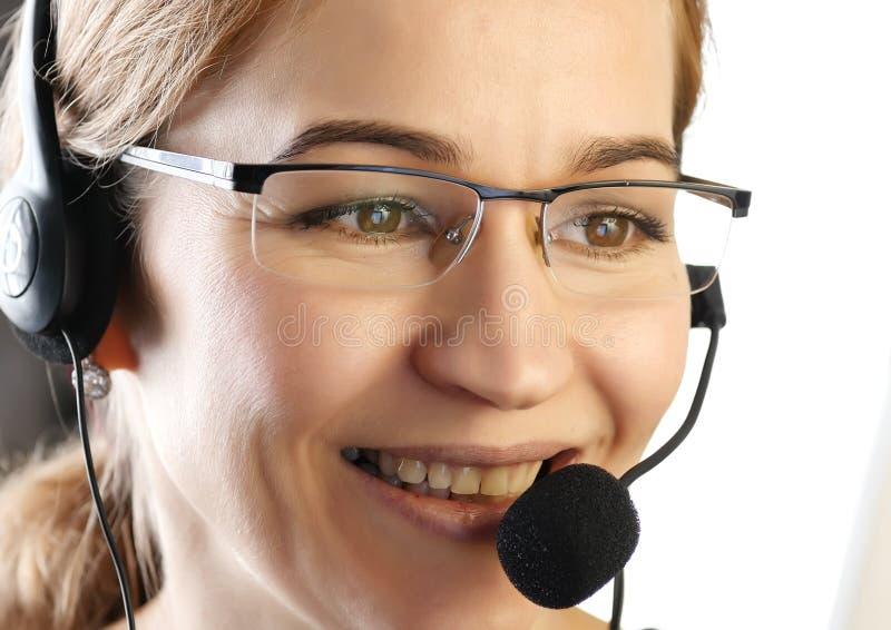 Affärskvinna som talar på en hörlurar med mikrofon i ett kontor kundtjänstproffessional arkivfoto