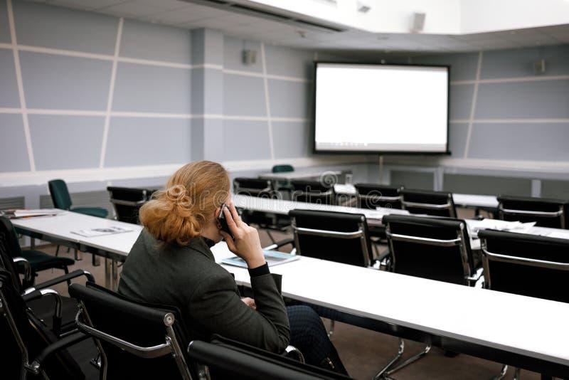 Affärskvinna som talar på en smartphone i en tom konferenskorridor arkivfoto