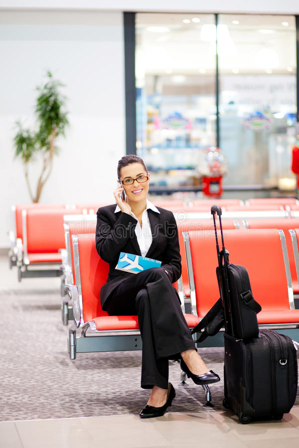 Affärskvinna som talar på flygplatsen arkivbilder