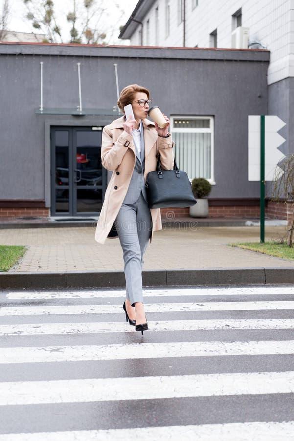 affärskvinna som talar på smartphonen och dricker kaffe, medan korsa vägen royaltyfri bild