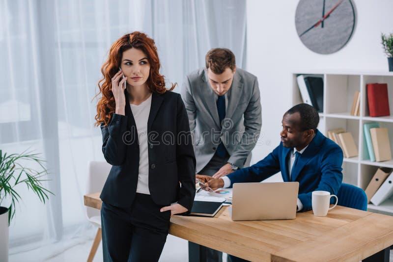 Affärskvinna som talar på smartphonen och två affärskollegor som gör skrivbordsarbete royaltyfria bilder