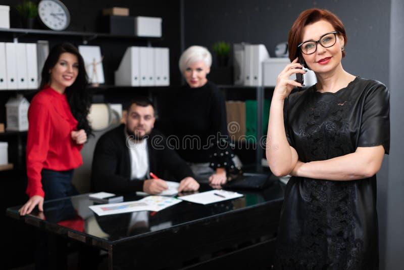 Affärskvinna som talar på telefonen på bakgrund av kontorsarbetare som diskuterar projekt royaltyfri foto