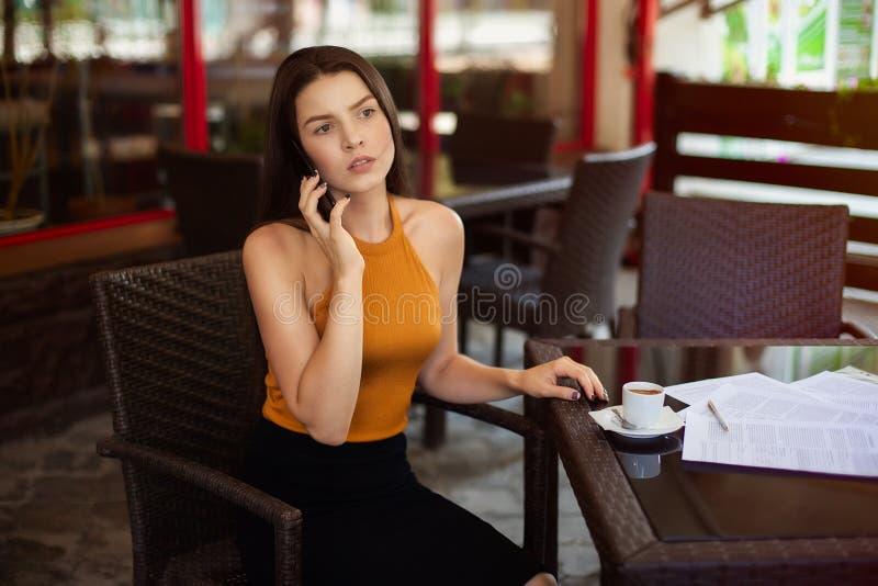 Affärskvinna som talar på telefonen i ett kafé på en tabell med spridd legitimationshandlingar på tabellen och en kopp kaffe royaltyfria foton