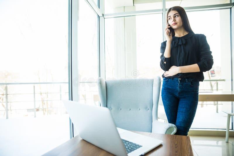 Affärskvinna som talar på telefonen nära tabellen och ser fönstret royaltyfri foto