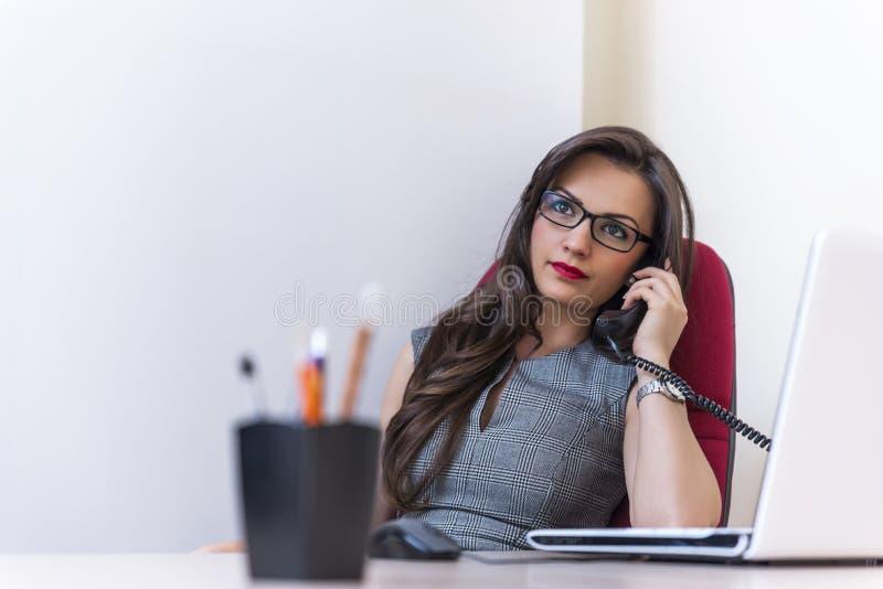 Affärskvinna som talar på telefonen och använder hennes bärbar dator arkivfoton