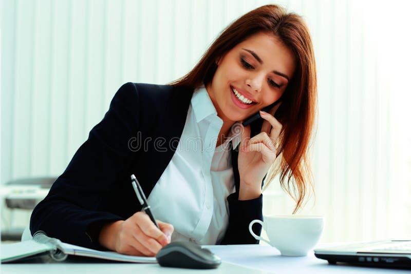 Affärskvinna som talar på telefonen och skriver anmärkningar arkivfoto