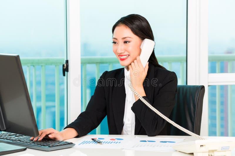 Affärskvinna som talar på telefonen som ser datoren fotografering för bildbyråer