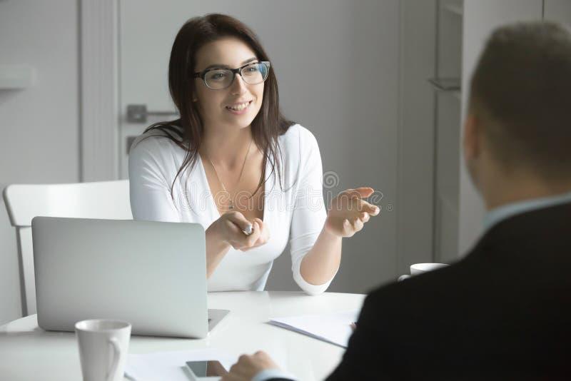 Affärskvinna som talar till en man på skrivbordet royaltyfri fotografi